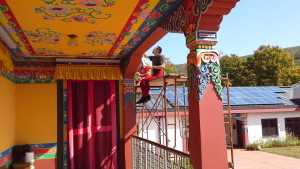 photo of a man painting the KTD Tibetan monastery in Woodstock, NY