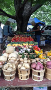 This is an out door flea market with a table displaying fresh vegetables and fruit