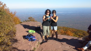 Two women hikers toasting wine glasses at the top of Overlook Mt.