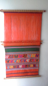This is a colorful hand woven wall hanging with an orange background from Comalapa, Guatemala