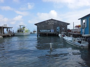 "Photo of the dock at Ambergris Caye, Belize with a funny sign saying ""No Work During Drinking Hours."""