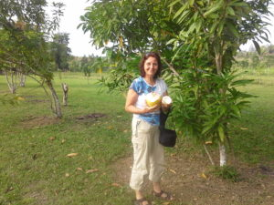 Photo with a woman under a tree holding an open fresh coconut on a farm in Cayo Belize