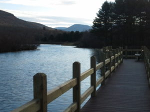 This is a photo of a wooden pier looking over a lake with of view of the mountains ahead. Taken at Kenneth Wilson State Park, NY