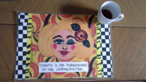 "photo of a placemat painting that says ""Sanity is the Playground of the Unimaginative"""