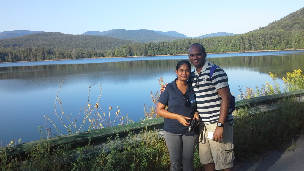 photo of an Indian couple against the backdrop of mountains and a blue lake