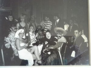 Black and white photo from the late 1940's of a mascarade ball given by the Woodstock School of Art in Woodstock NY. It looks like the costumed students are sitting in a home or restaurant.