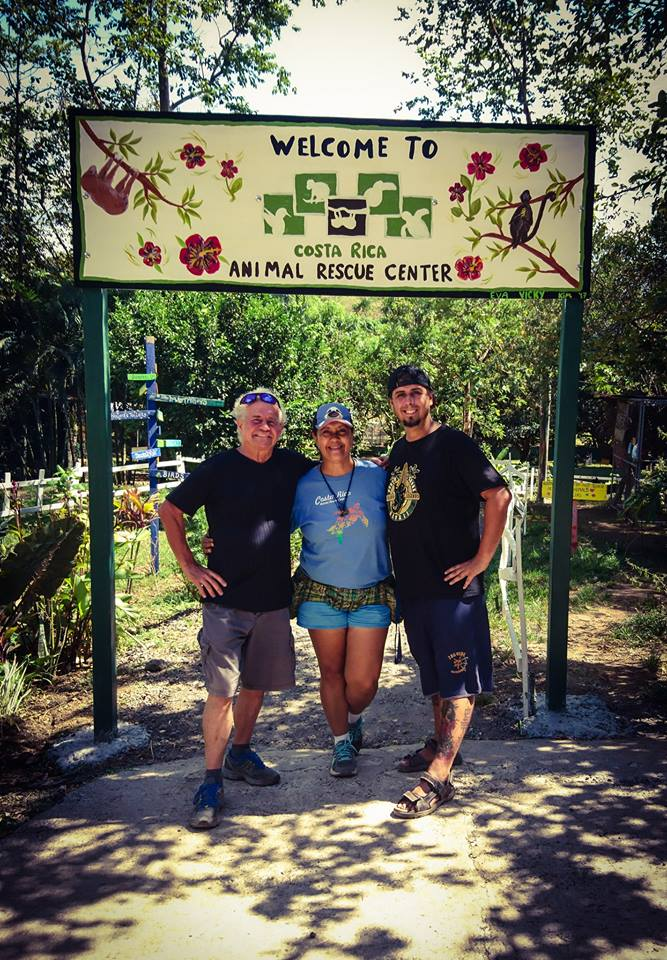 "One woman and two men standing beneath a big sign saying ""Welcome to the Costa Rica Animal Rescue Center"""