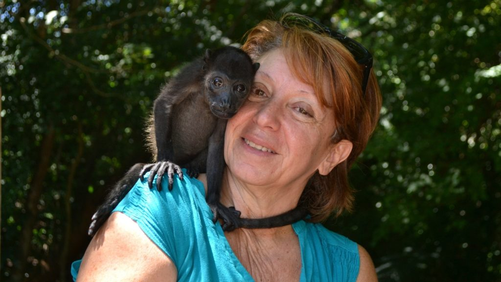 This is a photo of a woman smiling with a baby black howler monkey on her shoulder